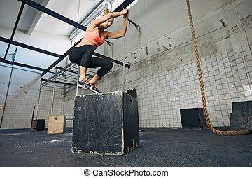 Der weibliche Sportler macht Boxspringen im Fitnessstudio