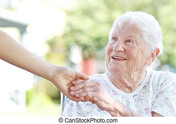 Die ältere Frau, die Händchen hält mit der Betreuerin