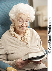 Die ältere Frau entspannt sich zu Hause und liest Bücher
