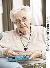 Die ältere Frau sortiert Medikamente mit Organisatoren zu Hause