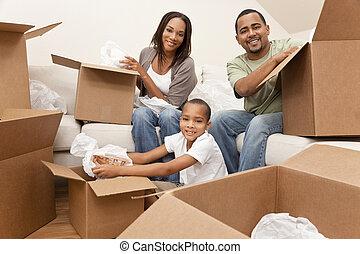 Die afrikanische amerikanische Familie packt Kisten aus, die sich bewegen