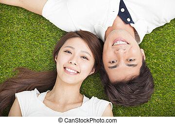 Die Aussicht auf junge Paare, die sich lieben, liegt auf dem Rasen.