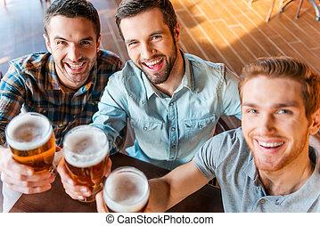 Die beste Aussicht auf drei glückliche junge Männer in zwangloser Kleidung, Toast mit Bier, während sie zusammen in der Bar sitzen.