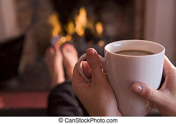Die Füße wärmen sich an einem Kamin mit Händen, die Kaffee halten