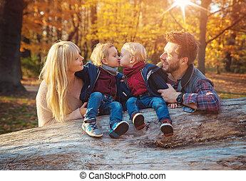Die Familie genießt ein Herbstwetter in einem Wald.
