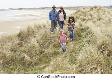 Die Familie läuft am Winterstrand entlang