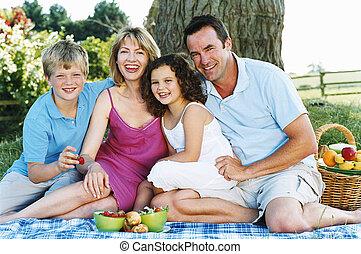 Die Familie sitzt draußen mit Picknick lächelnd