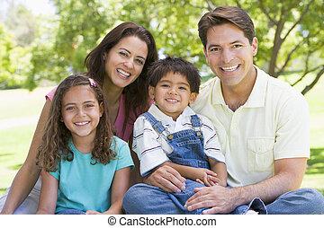 Die Familie sitzt draußen und lächelt
