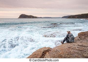 Die Frau, die am Meer sitzt und die Wellen zu ihren Füßen liegen lässt