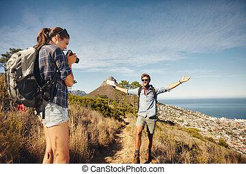 Die Frau fotografiert ihren Freund beim Wandern