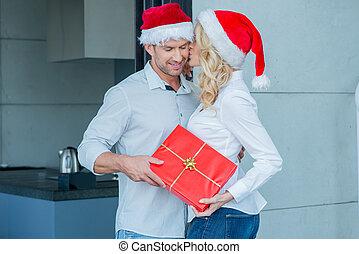 Die Frau küsst ihren Mann an Weihnachten.