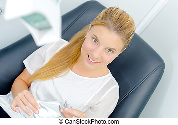 Die Frau saß in einem Zahnarztstuhl.