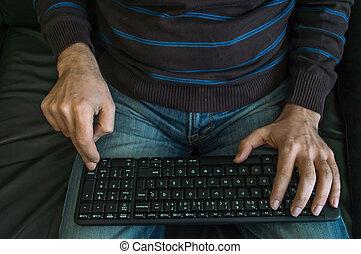 Die Hände des Mannes an der Tastatur.
