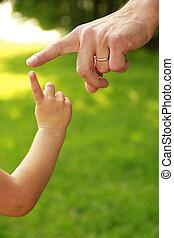 Die Hand von Eltern und Kind in der Natur.