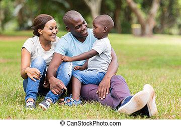 Die junge afrikanische Familie sitzt draußen.