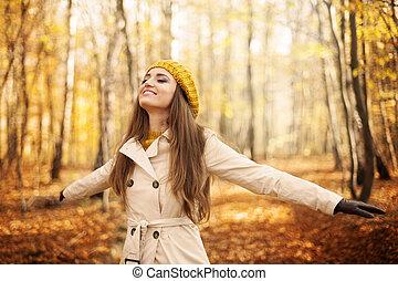 Die junge Frau genießt die Natur im Herbst.