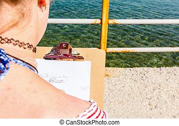 Die junge Frau ist mit einem Graphitstift auf einem Zeichnungsbrett.