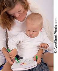 Die junge Mutter zeichnet mit ihrem Sohn