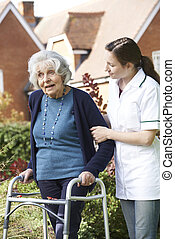 Die Pflegerin hilft älteren Frauen, im Garten zu laufen.
