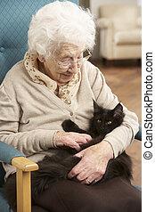 Die Seniorenfrau entspannt sich zu Hause mit Haustierkatze