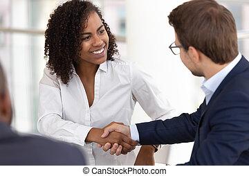 Die vielfältige Geschäftsfrau und der Geschäftsmann-Handschlag machen den Deal beim Treffen.