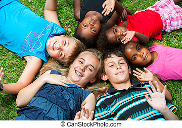 Diverse Gruppe og Kinder, die zusammen auf Gras.