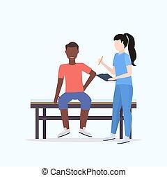 Doktor Holding Klemmbrett weibliche Therapeutin Beratung verletzt afroamerikanischen männlichen Patienten, die auf dem Bett manuell Sport Physiotherapie Konzept volle Länge.