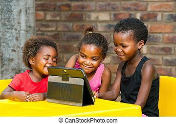 Drei afrikanische Kinder spielen zusammen auf einer Tafel.