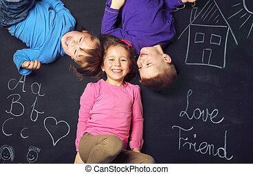 Drei fröhliche Kinder spielen zusammen.