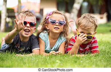 Drei fröhliche Kinder spielen zusammen