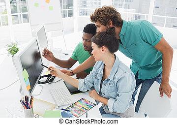 Drei Künstler arbeiten im Büro am Computer.