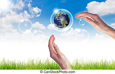 Eco-Konzept: Hand hält Globus in Blasen gegen die Sonne und den blauen Himmel