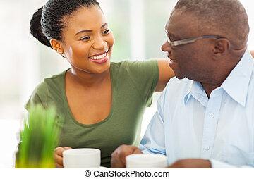 Ein älterer afroamerikanischer Mann, der mit seinem Großvater zu Hause Kaffee trinkt