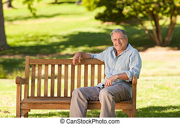 Ein älterer Mann, der auf einer Bank sitzt