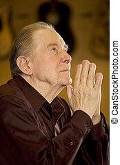Ein älterer Mann, der in der Kirche betet