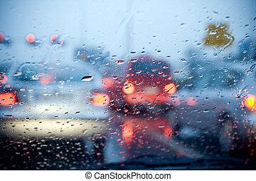 Ein Auto fährt in einem Regensturm mit verschwommenen roten Lichtern