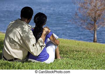 Ein Blick auf das afroamerikanische Paar, das am See sitzt