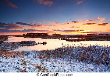 Ein bunter Sonnenaufgang über dem Fluss im Winter