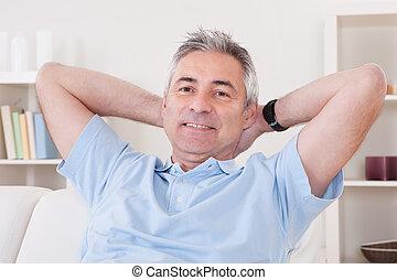 Ein erwachsener Mann sitzt auf dem Sofa