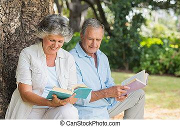 Ein erwachsenes Paar liest zusammen Bücher auf dem Baumstamm