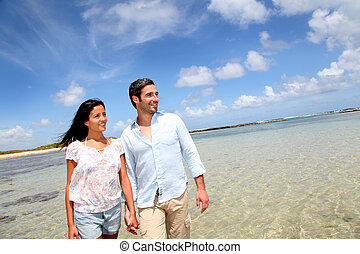 Ein fröhliches Paar, das am Meer vorbeiläuft.
