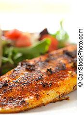 Ein ganzes gewürztes Fläschchen Weißfisch auf gemischtem Salat mit Tomaten
