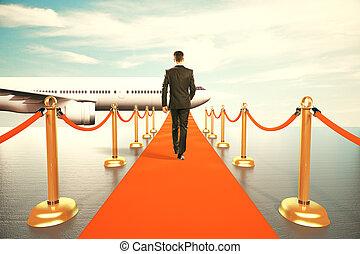 Ein Geschäftsmann, der auf dem roten Teppich zur ersten Klasse geht.