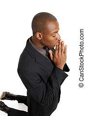 Ein Geschäftsmann, der auf Knien betet