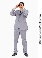 Ein Geschäftsmann lächelt, während er ein Fernglas benutzt