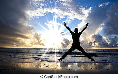 Ein glücklicher Mann springt mit schöner Sonne am Strand