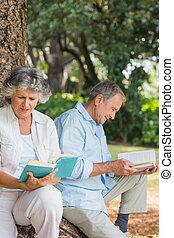 Ein glückliches älteres Paar, das zusammen Bücher liest und auf dem Baumstamm sitzt