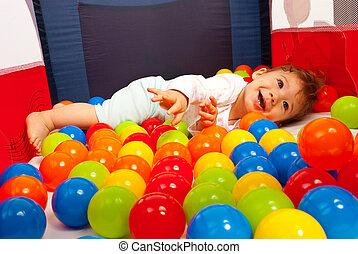 Ein glückliches Baby, das mit Bällen spielt