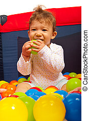 Ein glückliches Baby mit bunten Bällen