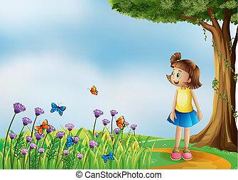 Ein glückliches Mädchen auf dem Hügel mit einem Garten